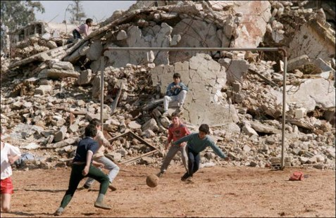 Palestinian children play soccer 06 February 1988 in the ruins of Chatila refugee camp, southern suburb of Beirut. In January 1988, avowedly as a gesture of support for the uprising by Palestinians resident in Israeli-occupied territories, which had begun in December 1987, Nabih Berri, the leader of Moslem Shi'ite Amal militia, announced the ending of the siege of the Palestinian refugee camps in Beirut and southern Lebanon. 27 June 1988, the Arafat loyalist in Chatila camp were overrun and surrendered to the fighters belonging to the Syrian-backed group, al-Fatah Intifada (Fatah Uprising) of Abu Musa. The following day Syria granted 100 PLO guerrillas safe passage from Chatila to the camp at Ain al-Helweh. 07 July, Bourj el-Barajneh, Arafat's last stronghold in Beirut, was captured by the forces of Abu Musa, and 120 PLO fighters were evacuated to Ain al-Helweh refugee camp. (FILM) (Photo credit should read NABIL ISMAIL/AFP/Getty Images)